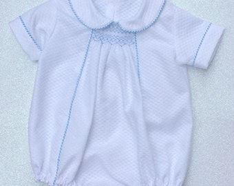Baby boy's white smocked summer romper with pale blue piping. Available from birth to 18 months
