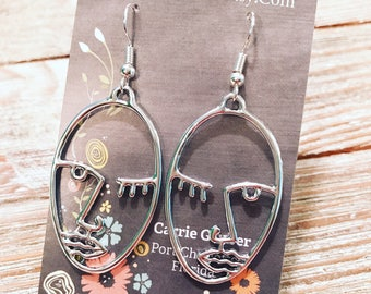 Silver tone Picasso face earrings on nickel free ear wires.