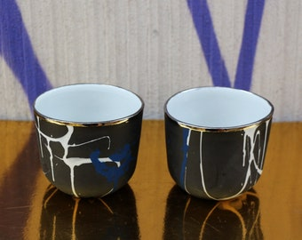 Two porcelain tumblers made of white grey and blue ceramics with platinum rim tea or coffee set