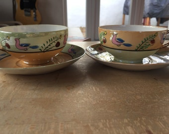 A set of two delicate hand painted tea cup and saucer sets made in Japan circa 1940's