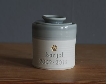 custom pet urn. gold infilled stamp with ceramic lid, straight shaped urn with heart stamp. modern simple urn for ashes. dove grey urn.