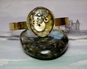 Ajustable gold colour steampunk bracelet,  crystal clear resin  with inclusions  of watch cogs and  electronic circuit  Unique piece