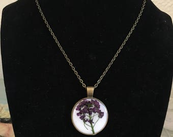 Round bronze pendant with real purple wildflowers