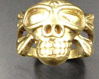 Pirate skull and crossed bones on a brass ring.