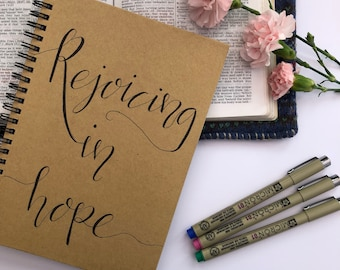 A5 Kraft Notebook with a Hand Lettered Scripture Verse.