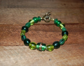 Handmade green and gold beaded bracelet with toggle clasp