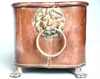 A copper planter with brass lion heads and paw feet.