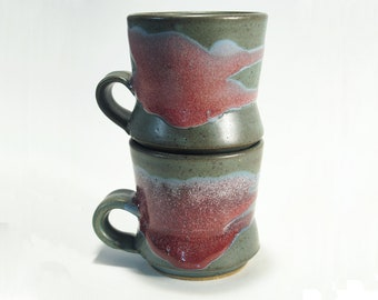 Small coffee or tea cups, beautiful rich blue-green surface with red accents