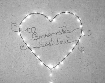 Bright heart, wall decor, surrounded by a string of lights operated message writing in wire