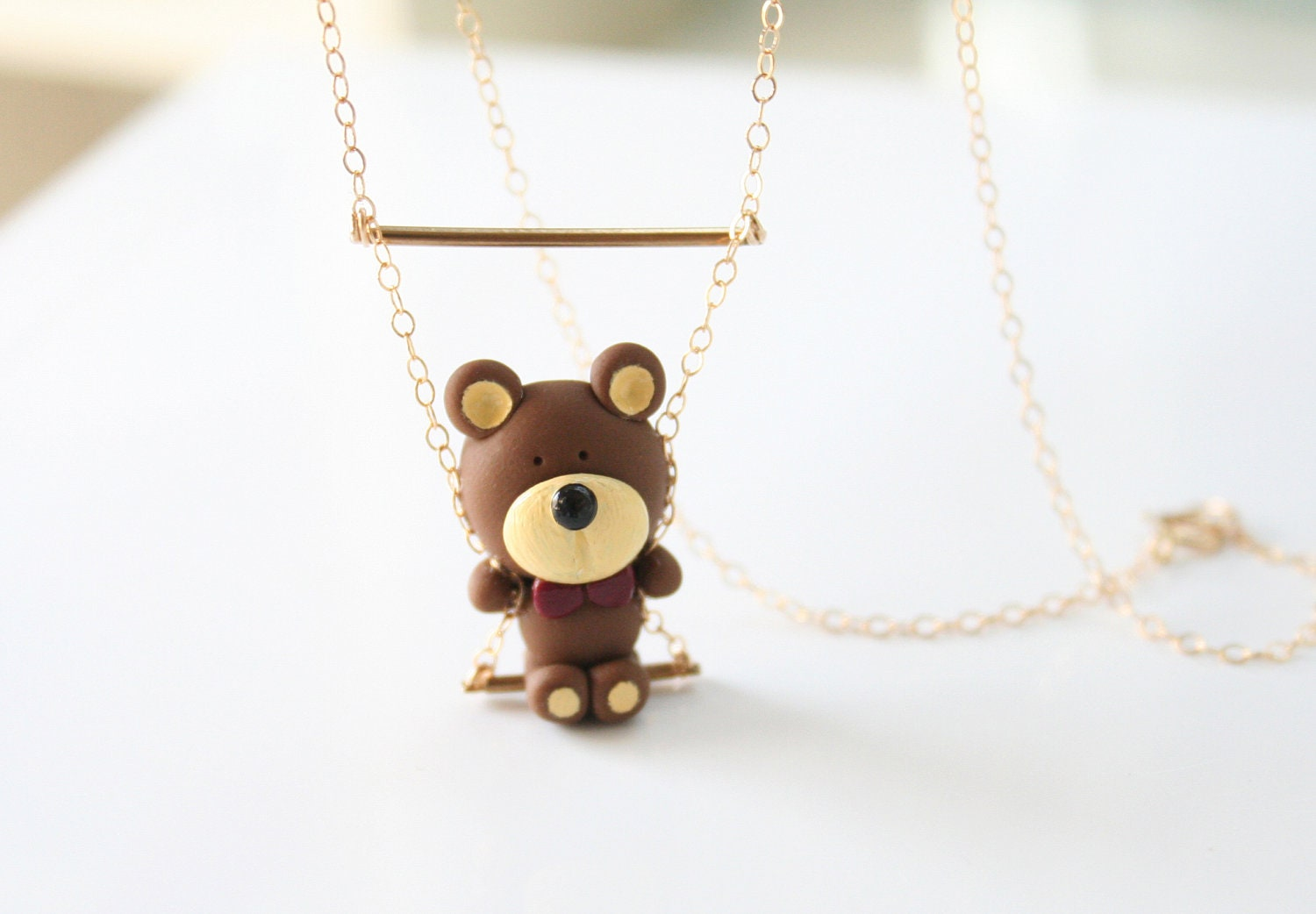 Bear swinging on gold chain necklace