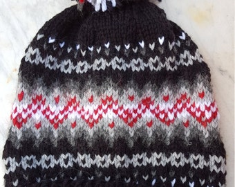Beanie, winter hat with Fair Isle design in soft warm wool,  Black with red and white design and topped with a pom pom.