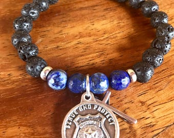 Police officer prayer yoga bracelet in lava stone and lapis lazuli gemstone beads and shield charm with Saint Michael on reverse side.
