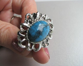 Silver tone metal and turquoise cabochon ring.This is an expandable ring. It could be worn on a size 5-10 finger.Silvertone Turquoise Ring