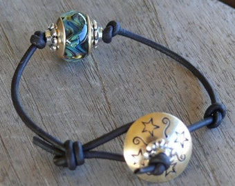 Boro Lampwork & Brass bracelet w/hand stamped brass and distressed leather cord, gold, blues, greens, silver