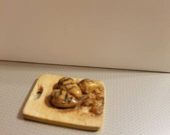 Dollhouse miniature grilled chicken on a cutting board