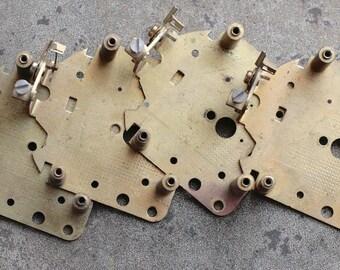 Four large vintage alarm clock parts -- brass