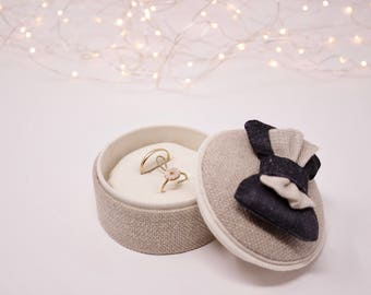 Linen ring bearer with a warm grey and beige layered bow.