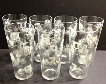 Group of 7 mid-century glass tumblers, clear glass with white horseless carriages pattern, 6 1/2 inches tall.