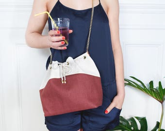 Gisele: bucket bag made of off-white linen and terra-cotta, golden chain.