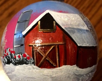 Hand painted glass ornament with a winter barn scene