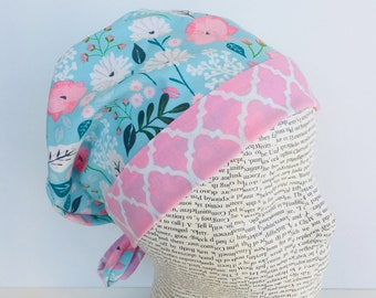 Tie Back Scrub Cap scrub hat featuring a light blue material with flowers in pink and white with a coordinating band 2t