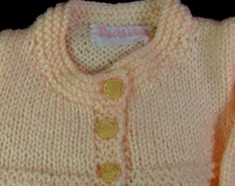 A baby soft peach hand knitted lacy jersey, weater, cardigan, jumper for 6-9 month old baby girls.