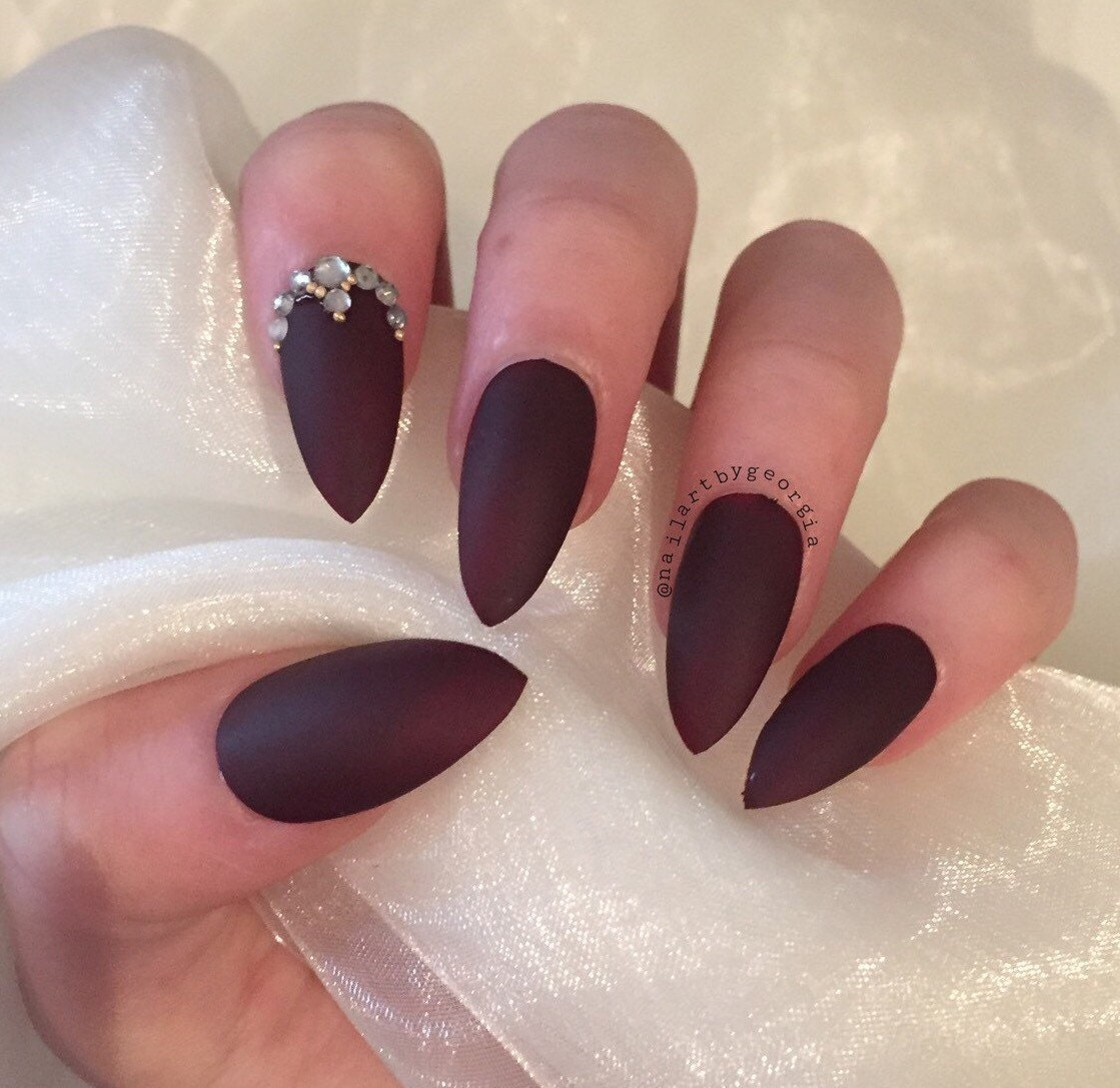 Burgundy matte stiletto nails with rhinestone and gold bead