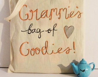 """Grammie's Tote - A natural cotton hand painted tote with """"Grammie's bag of Goodies"""" in coral and black cursive. Customizable Tote"""
