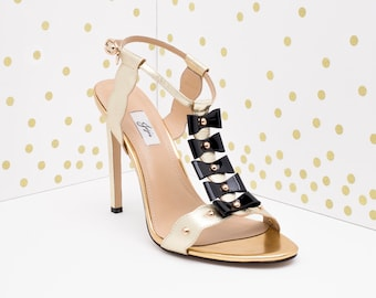 Gold T-strap sandals with black bows and studs