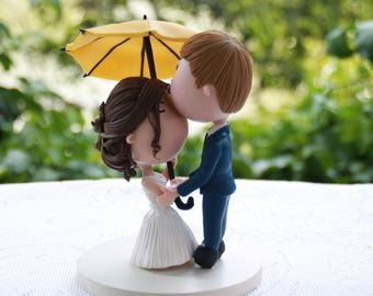 Couple Kissing under yellow umbrella. Handmade. Fully customizable. Unique keepsake. Wedding cake topper.