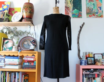 1960s. black wool wiggle bombshell dress with netted sleeves. size medium-large
