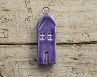 A handmade ceramic purple house pendant