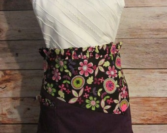 Purple and floral print half apron with ruffled waistband and a pocket