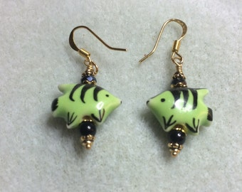 Green and black ceramic fish bead earrings adorned with black crystal and glass beads.