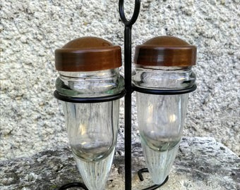 glass salt and pepper with plastic lids in wrought metal holder.