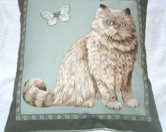 Lovely plush Persian cat sitting with butterfly on pale green cushion