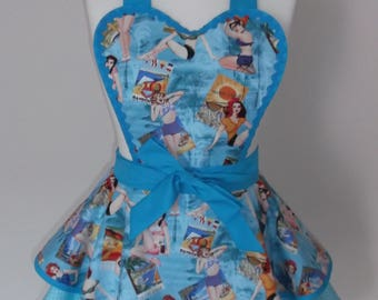 1950s style retro apron pinny in vintage style 'vacation pin-up models' print and blue polka dot fabric