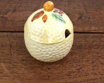 Vintage sugar bowl or jam pot, dimpled glaze ceramic with fruit and flower decoration on the lid