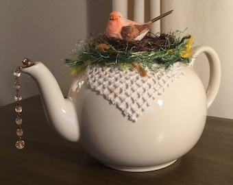 Pristine of England-cream white teapot-peach bird-nest-variegated green yarn-vintage doily piece-pink crystal strand-spout-Easter-spring-egg