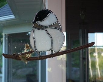 A bird (chickadee) on a branch stained glass