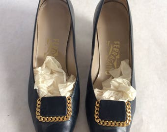Navy Ferragamo pumps with gold embellishments