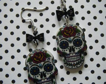 White detailed sugar skull earrings with black bows on silver ear wires
