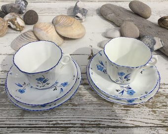 Two trios of vintage Cartwright and Edwards hand painted bone china cups saucers and side plates