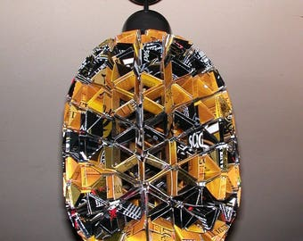 """""""Bee"""" made of recycled cans hanging"""