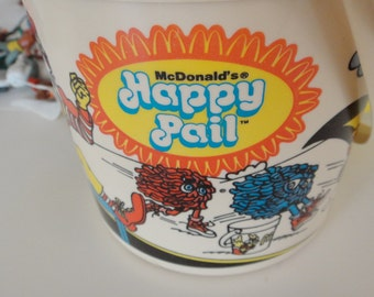 1983 McDonald's Happy Pail filled with vintage plastic cowboys and indians