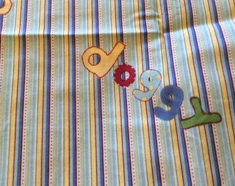 Blue green yellow Burgandy, and white striped cotton fabric with doggy written all over it