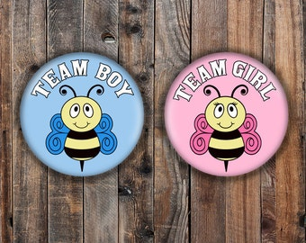 Baby bee team boy and team girl gender reveal pins with light pink and blue backgrounds.