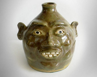 Clay folk art pottery jug with face and clay teeth