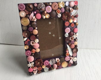 Purple picture frame with pink, peach, pearl, brown and burgundy buttons