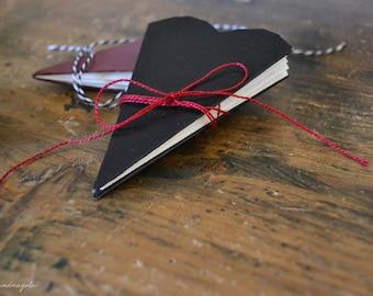 Libro nero a forma di cuore. Biglietto illustrato per San Valentino. Biglietto di fidanzamento a forma di cuore.